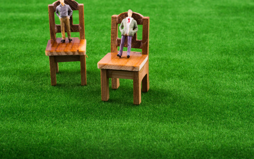 Men figures on wooden toy chairs on artificial grass